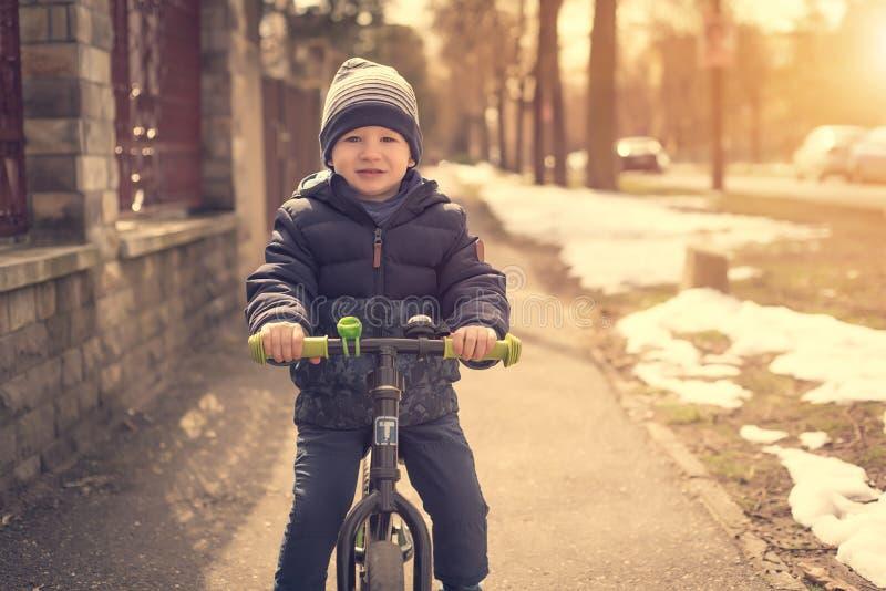 Ung pojke i parkera med hans rinnande cykel arkivbild
