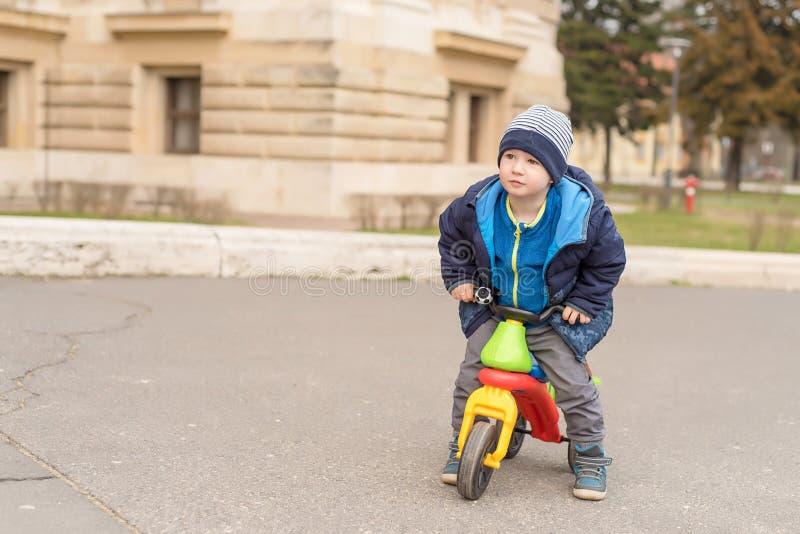 Ung pojke i parkera med hans rinnande cykel arkivfoto