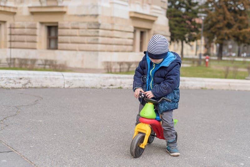 Ung pojke i parkera med hans rinnande cykel royaltyfria bilder