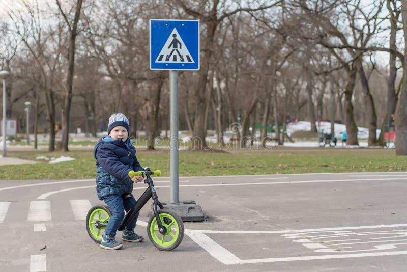 Ung pojke i parkera med hans rinnande cykel royaltyfri bild