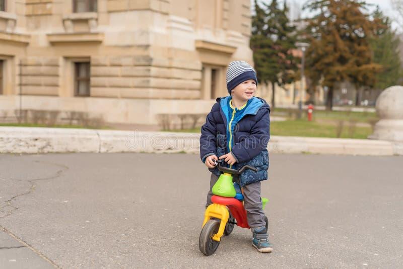 Ung pojke i parkera med hans rinnande cykel royaltyfri fotografi