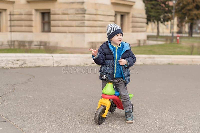 Ung pojke i parkera med hans rinnande cykel fotografering för bildbyråer
