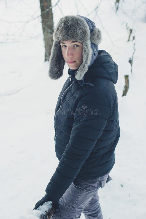 Ung pojke i vinterkläder med den varma hatten arkivbild