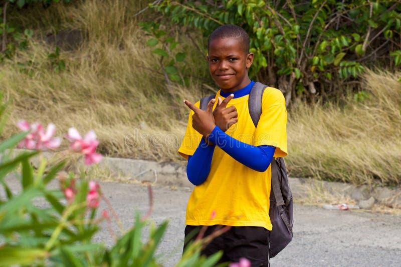 Ung pojke - lokaler i Bequia, granatäppelsafter som är karibiska arkivbild