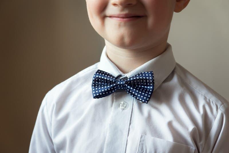 Ung pojke med den blåa flugan royaltyfria foton