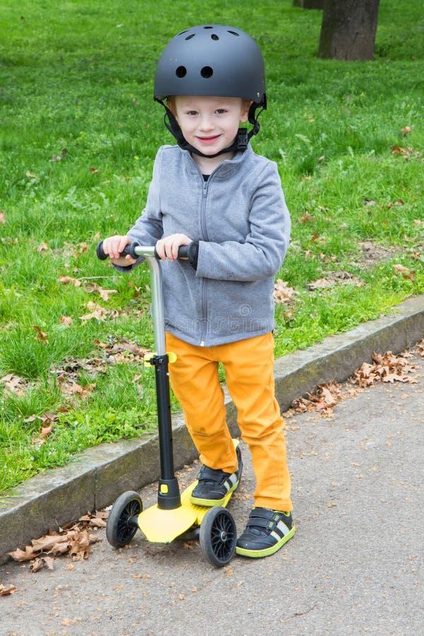 Ung pojke med den gula sparkcykeln på parkera arkivfoto