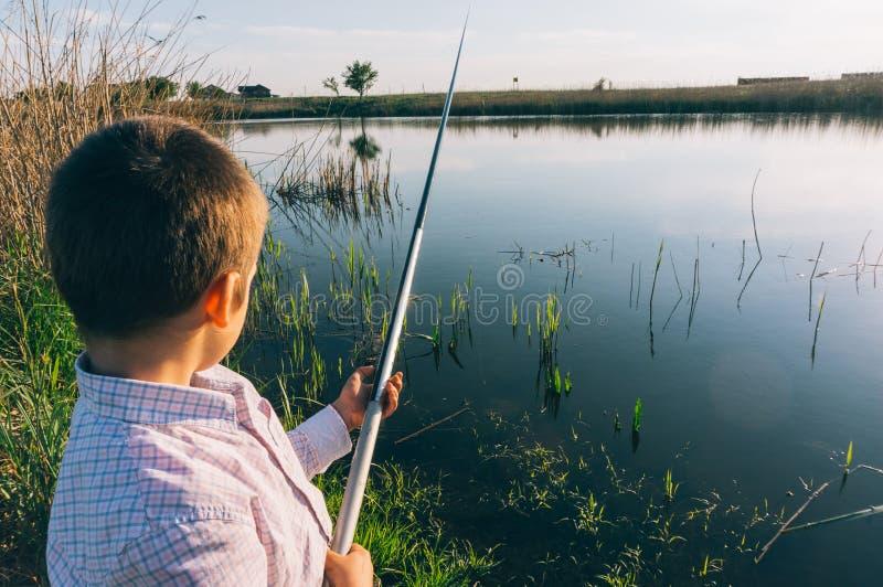 Ung pojke med fiskepolen royaltyfri fotografi