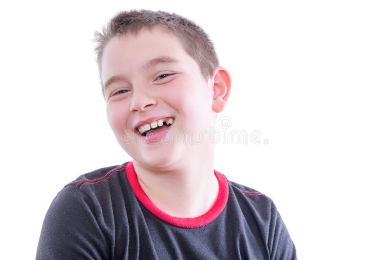 Ung pojke med hänglsen på tänder som skrattar i studio royaltyfri bild