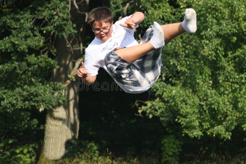 Ung pojke, med kortslutningar och skjorta som ner faller, från högt träd arkivfoton