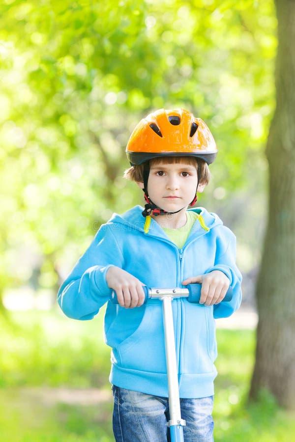 Ung pojke med sparksparkcykeln royaltyfria bilder
