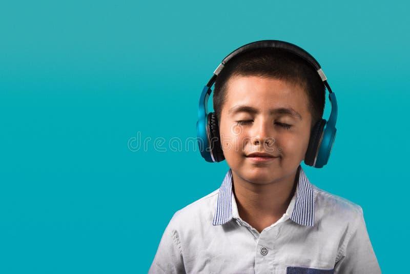 Ung pojke med stängda ögon och att le, lycklig bärande hörlurar som lyssnar till musikslutet upp ståenden med blå bakgrund royaltyfri bild