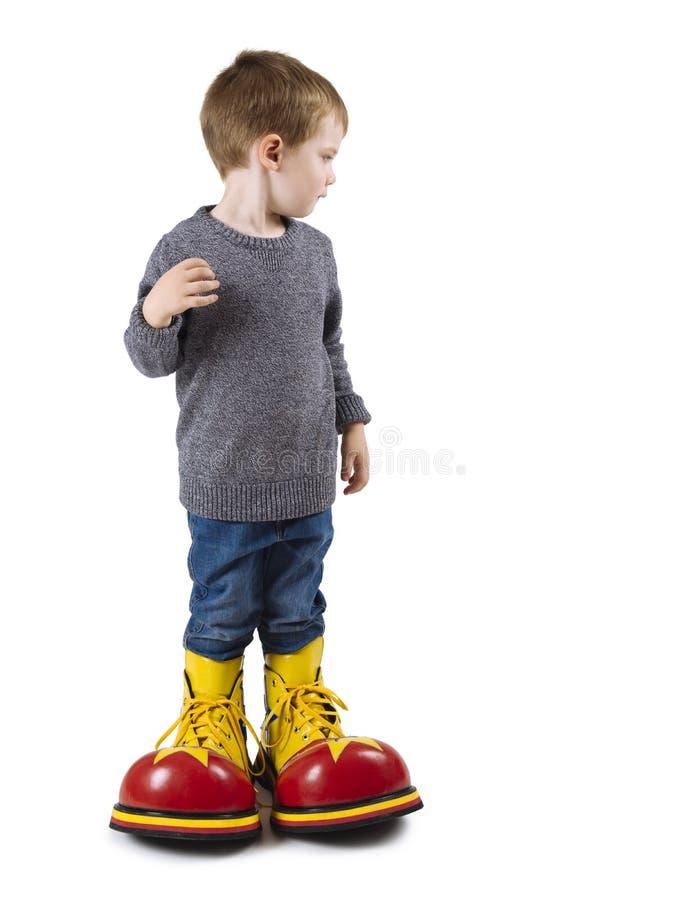 Ung pojke med stora clownskor arkivfoton