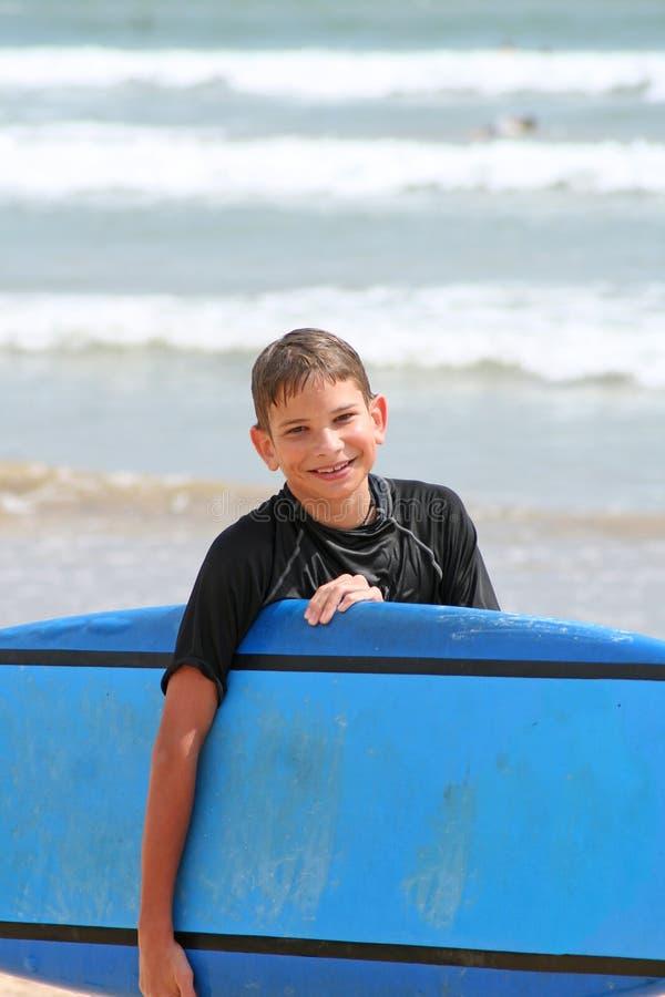 Ung pojke med surfingbrädan royaltyfri fotografi