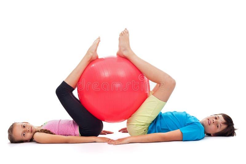 Ung pojke och flicka som övar med en stor gymnastisk rubber boll fotografering för bildbyråer