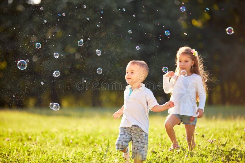 Ung pojke och flicka som ser såpbubblor royaltyfria foton