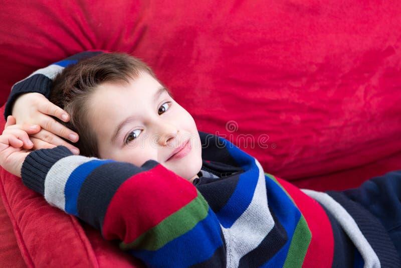 Ung pojke på den röda soffan royaltyfri fotografi