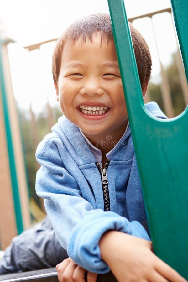 Ung pojke på klättringram i lekplats arkivbild