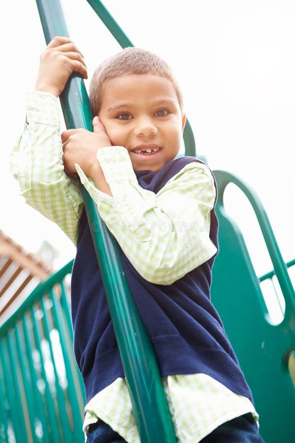 Ung pojke på klättringram i lekplats royaltyfri foto
