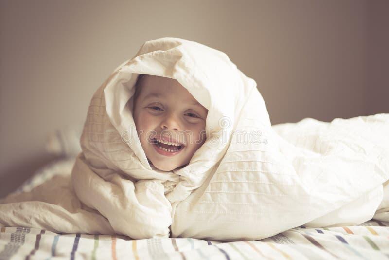 Ung pojke på säng arkivbild