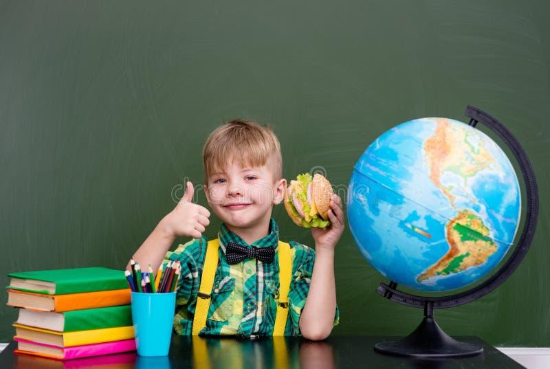 Ung pojke på skolainnehav- och visningtummar upp royaltyfri bild