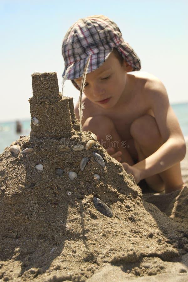 Ung pojke på stranddanandesandslott royaltyfri fotografi