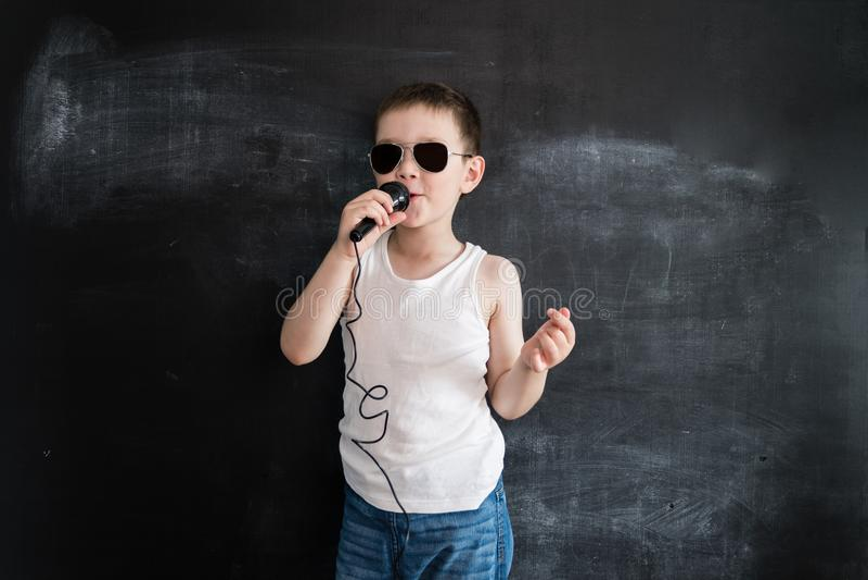 Ung pojke` s som står den near svart tavla som sjunger i mikrofon Rockstar Idérikt designbegrepp av det framtida yrket royaltyfria foton