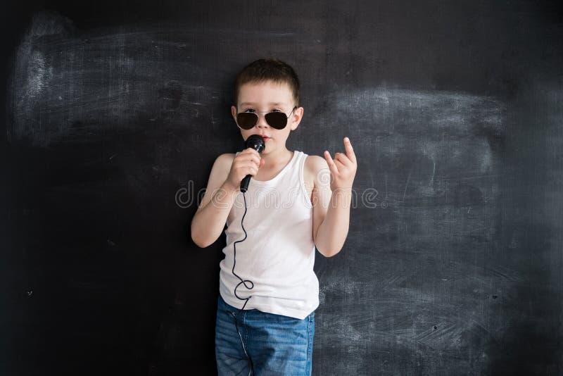Ung pojke` s som står den near svart tavla som sjunger i mikrofon Rockstar Idérikt designbegrepp för kalender 2019 arkivfoto