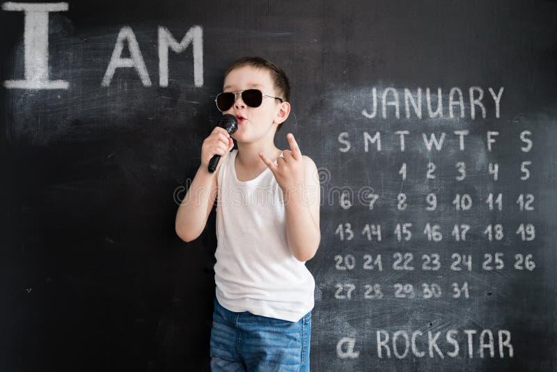 Ung pojke` s som står den near svart tavla som sjunger i mikrofon Rockstar Idérikt designbegrepp för kalender 2019 januari fotografering för bildbyråer