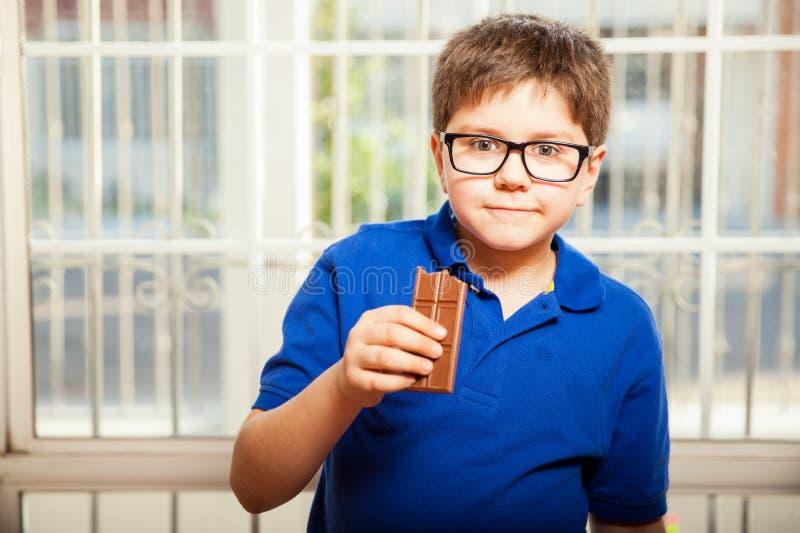 Ung pojke som äter choklad royaltyfria foton