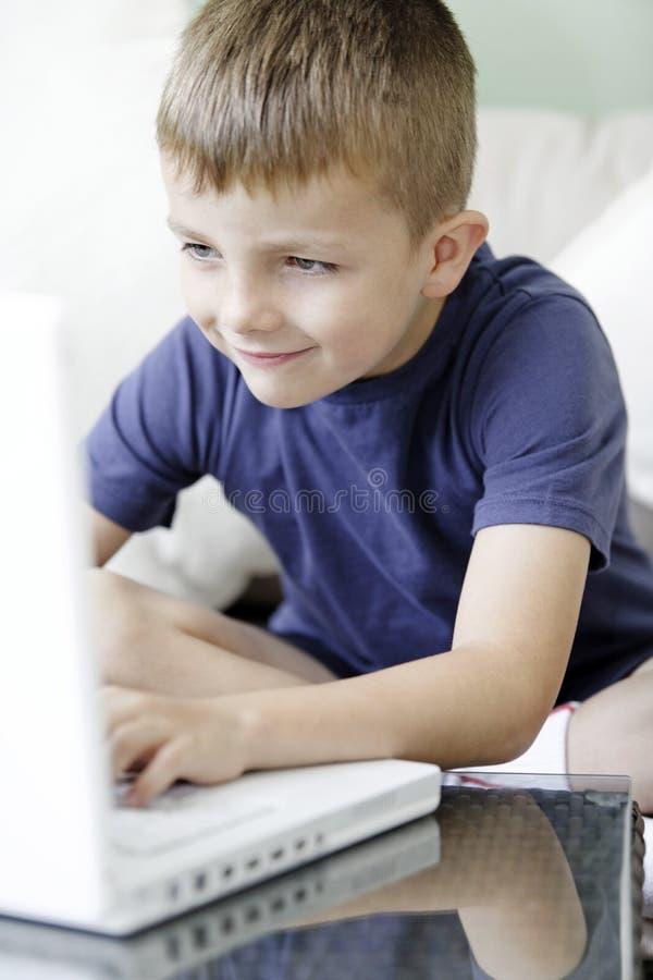 Ung pojke som använder en bärbar datordator arkivbilder