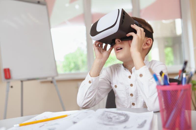 Ung pojke som använder hörlurar med mikrofon för virtuell verklighet 3d på skola royaltyfria bilder