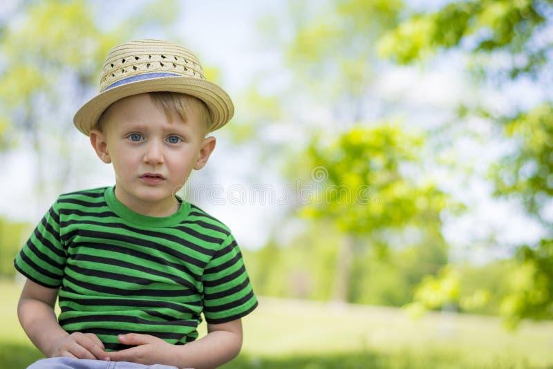 Ung pojke som bär en fedora på parkera fotografering för bildbyråer