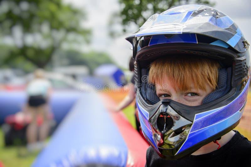 Ung pojke som bär en motorcykelhjälm arkivbilder