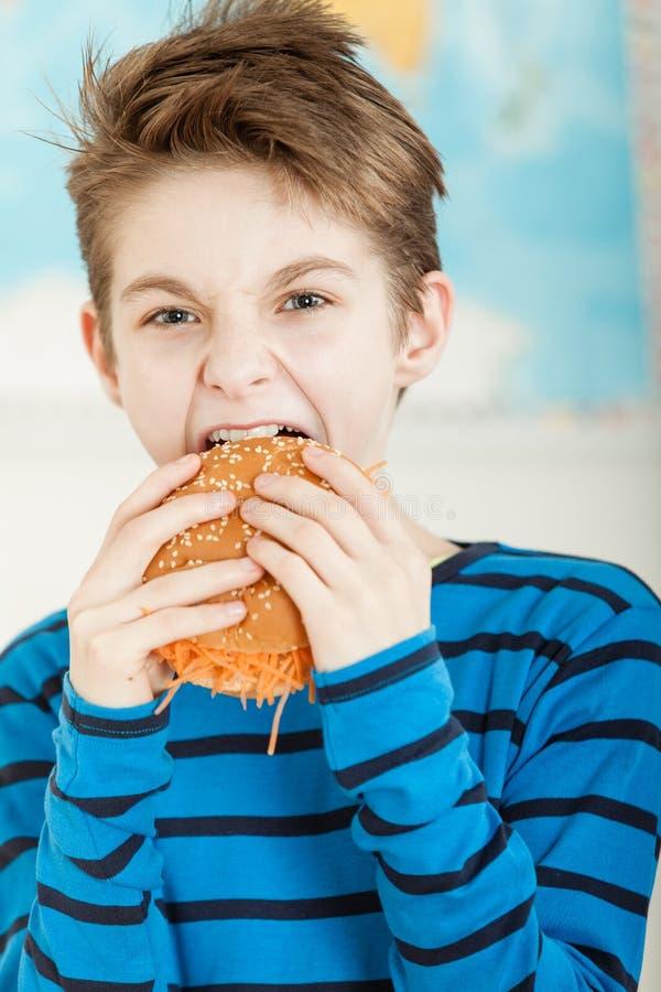 Ung pojke som biter in i en sesambulle royaltyfri fotografi