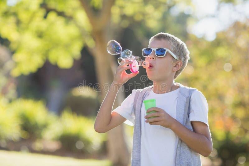 Ung pojke som blåser bubblor till och med bubblatrollstaven arkivbild