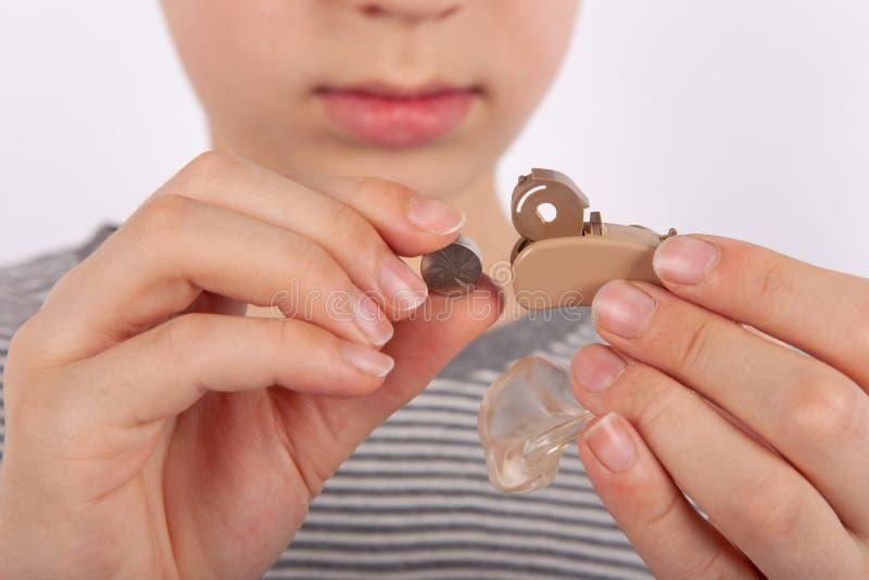 Ung pojke som byter ut ett hörapparatbatteri arkivfoto