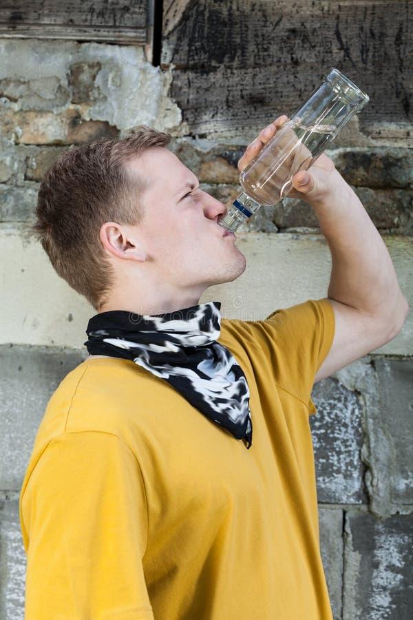 Ung pojke som dricker vodka royaltyfri fotografi