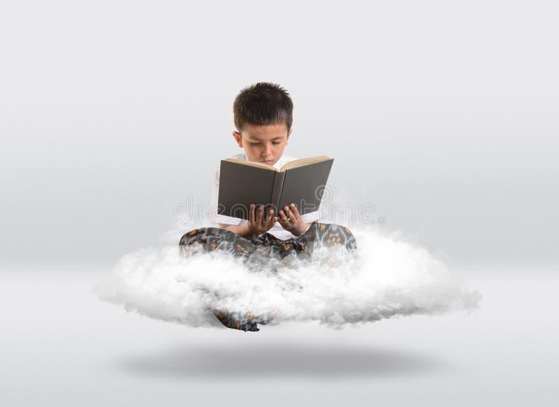Ung pojke som får att sväva på molnet, medan läsa en bok stock illustrationer