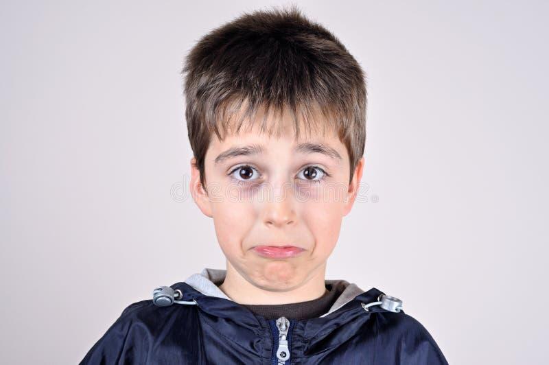 Ung pojke som gör en rolig framsida arkivfoto