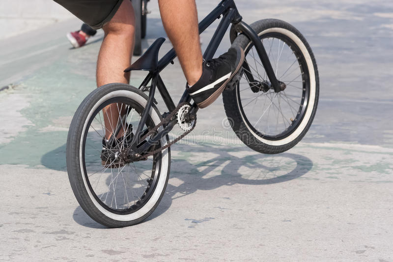 Ung pojke som gör ett trick med hans BMX-cykel nära ramper arkivbild