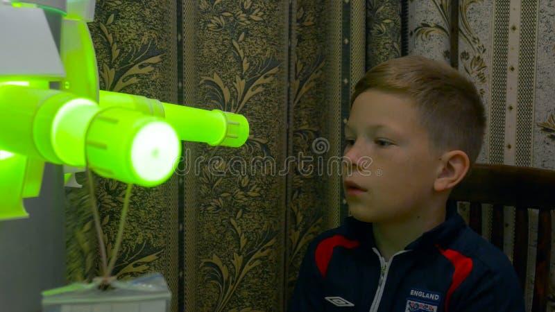 Ung pojke som genomgår behandling i modern klinik laser-inandning ljus UV inandningbehandling av halsen arkivbilder