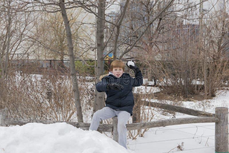 Ung pojke som kastar en kasta snöboll royaltyfria foton