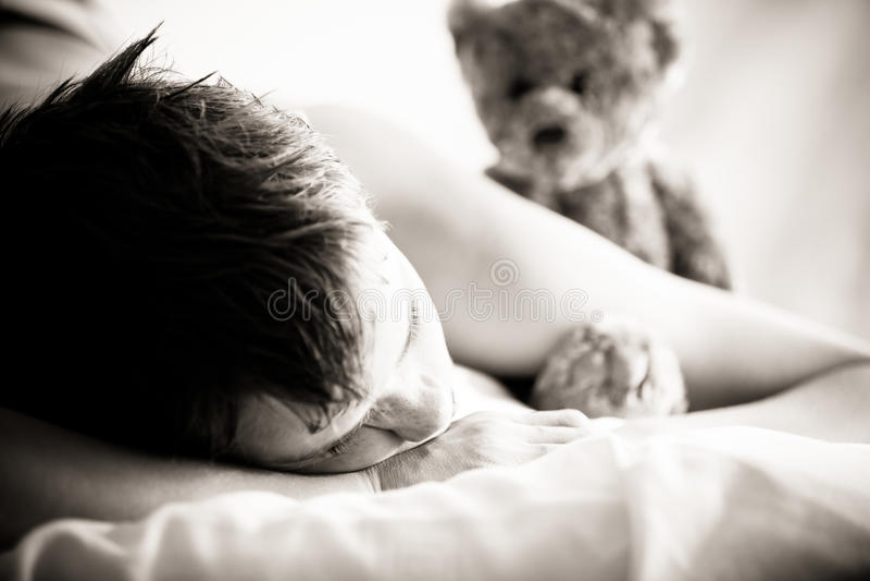 Ung pojke som ligger på säng med Teddy Bear royaltyfri fotografi