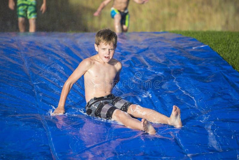 Ung pojke som ner utomhus glider en snedsteg och en glidbana arkivfoton