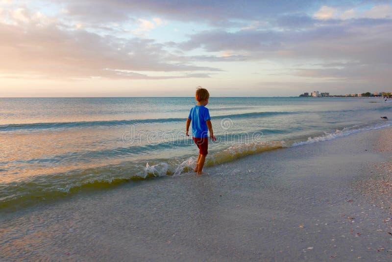 Ung pojke som promenerar kanten för vatten` s på en strand på solnedgången arkivfoton