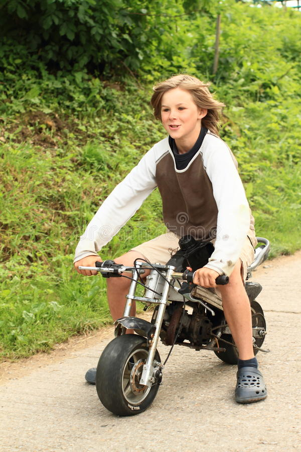 Ung pojke som rider den lilla mopeden arkivfoto