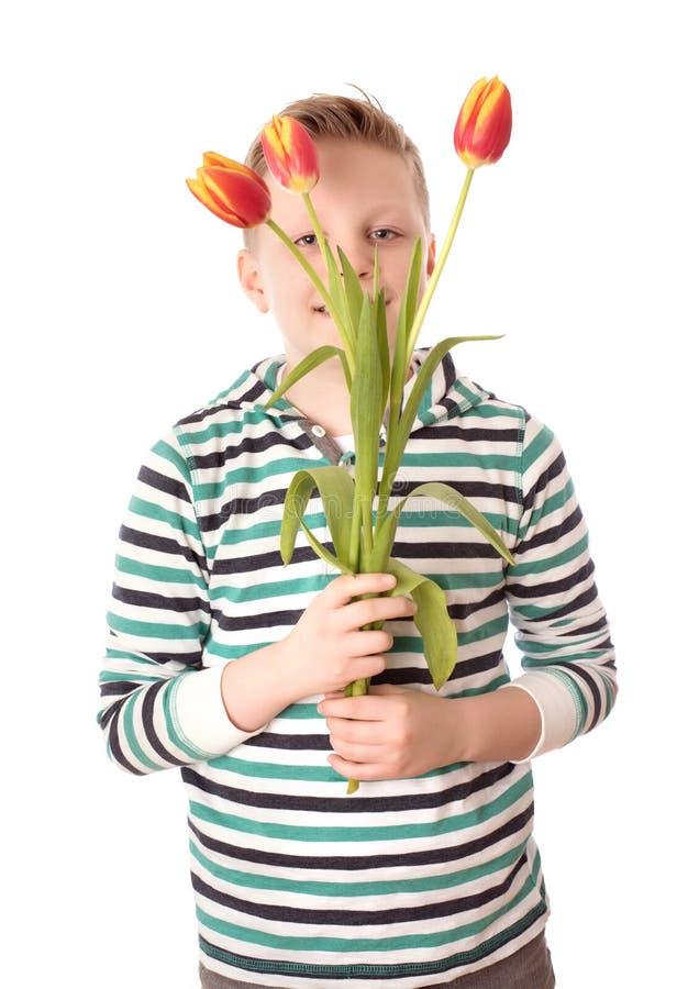Ung pojke som rymmer en tulpan över viten royaltyfria bilder
