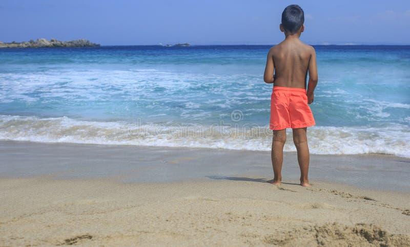 Ung pojke som ser havet fotografering för bildbyråer