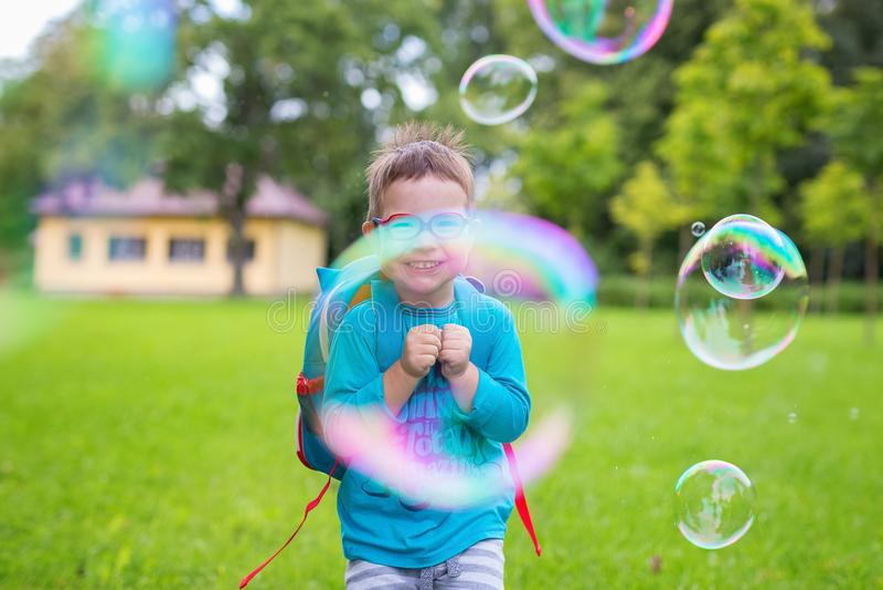 Ung pojke som ser till och med le för bubbla Sommar utomhus- grön lawn fotografering för bildbyråer