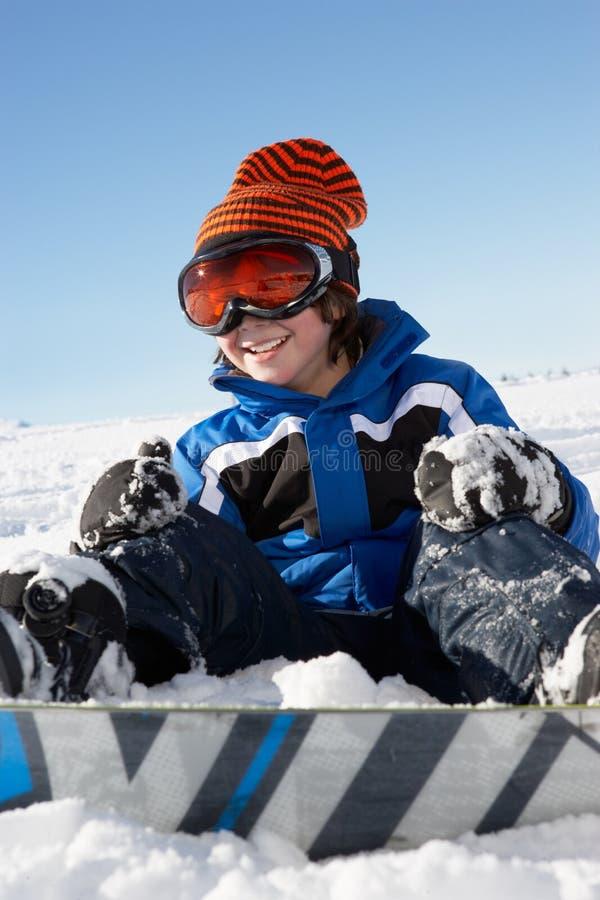 Ung pojke som sitter i Snow med snowboarden arkivbild